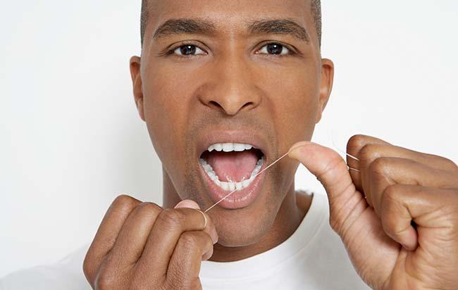 取一段长15-25cm的牙线,两端并拢打结形成一个线圈。  或取35-45cm长的牙线,将线的两端缠绕在双手的中指第二指节,约两三圈,可固定牙线即可。用双手的示指和拇指一起绷紧牙线,且通过手指头多肉的地方,使牙线在两指间相距1-1.5cm,同时此两指为打直的,指甲对指甲。将此段牙线轻轻通过两牙之间的接触区域,当有紧而通不过的感觉时,可做拉锯式动作,通过接触点,将牙线沿牙齿轻柔地滑进龈沟底(牙齿与牙龈交接的缝内),注意不要过分加压,以免牙线被硬压入龈沟以下过深的组织内,损伤牙龈。  将牙线紧贴一侧牙面的颈